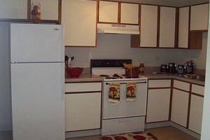 Kitchen, white cabinets with brown trim, white applicances