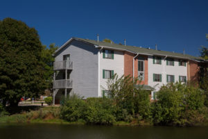 exterior building, balconies, trees, pond